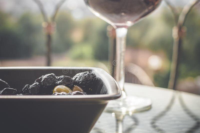 Κλείστε επάνω των ελιών στο μαύρο κύπελλο και του κόκκινου κρασιού στο γυαλί κρασιού στον πίνακα στοκ εικόνες