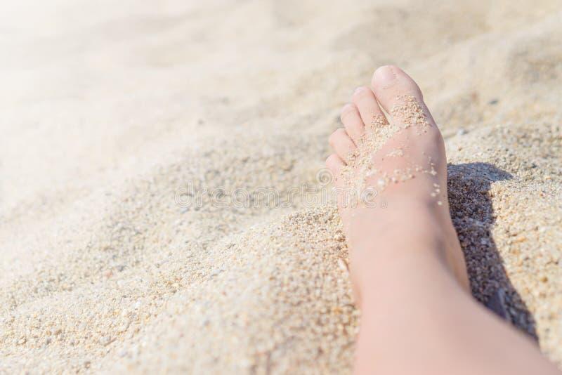 Κλείστε επάνω των θηλυκών ποδιών σε μια καυτή άμμο στην παραλία στοκ εικόνα