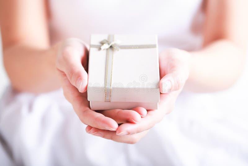 Κλείστε επάνω των θηλυκών χεριών κρατώντας ένα μικρό δώρο τυλιγμένο με το ribbo στοκ εικόνες