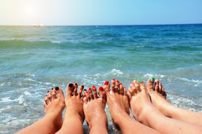 Κλείστε επάνω των λεπτών ποδιών τριών νέων κοριτσιών Μπλε θάλασσα στο υπόβαθρο, η έννοια παραθαλάσσιων διακοπών στοκ φωτογραφία με δικαίωμα ελεύθερης χρήσης