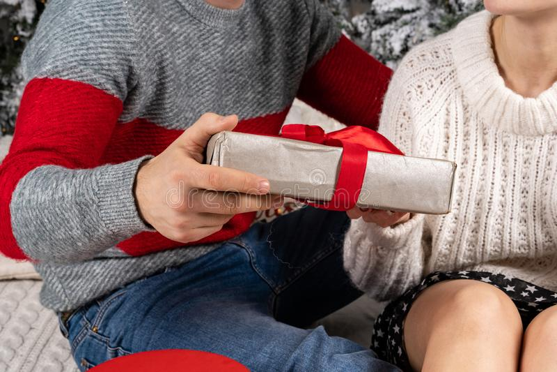 Κλείστε επάνω των νέων στα πουλόβερ που κρατούν τα δώρα στοκ εικόνες