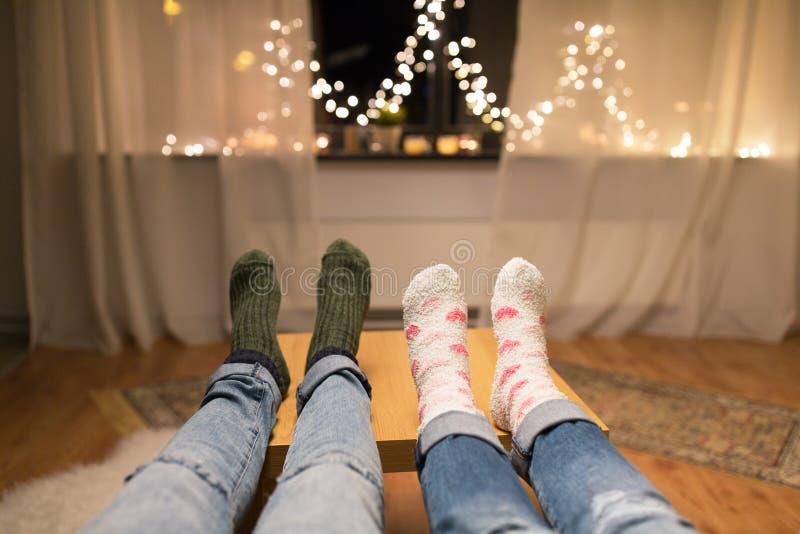 Κλείστε επάνω των ποδιών ζευγών και των φω'των γιρλαντών στο σπίτι στοκ εικόνες