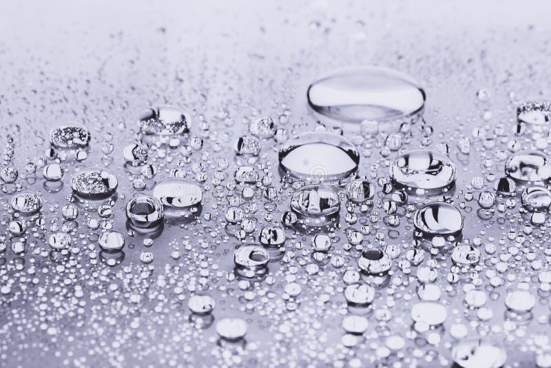 Κλείστε επάνω των πτώσεων νερού στο ασημένιο υπόβαθρο στοκ φωτογραφία