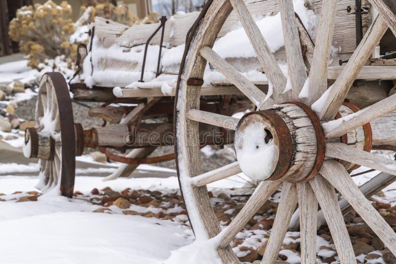 Κλείστε επάνω των σκουριασμένων ροδών ενός ξεπερασμένου ξύλινου βαγονιού εμπορευμάτων που αντιμετωπίζεται το χειμώνα στοκ εικόνες