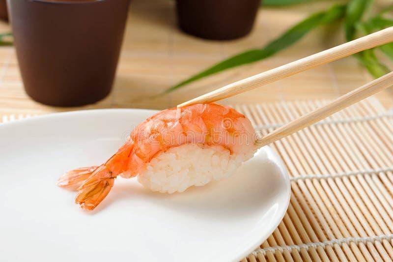Κλείστε - επάνω των σουσιών στη σάλτσα δύο chopsticks στοκ φωτογραφία