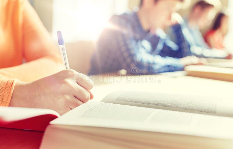 Κλείστε επάνω των σπουδαστών με τη σχολική δοκιμή γραψίματος βιβλίων στοκ εικόνες με δικαίωμα ελεύθερης χρήσης