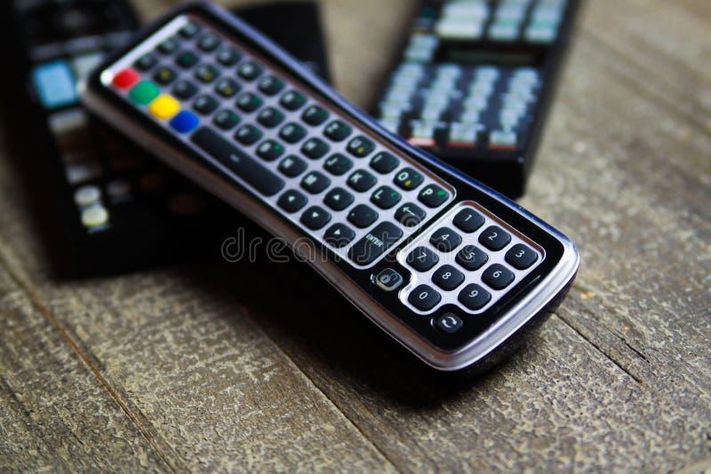 Κλείστε επάνω των τηλεχειρισμών για το τηλεοπτικού και στερεοφωνικού μουσικής σύστημα TV, στον ξύλινο πίνακα στοκ εικόνα