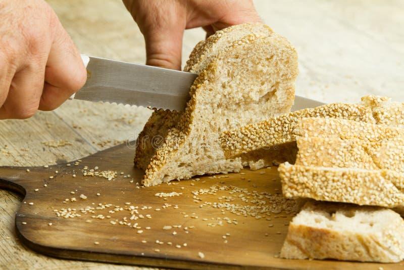 Κλείστε επάνω των χεριών ατόμων που τεμαχίζουν μια φραντζόλα του σπιτικού ψωμιού με τους σπόρους σουσαμιού σε έναν ξύλινο τέμνοντ στοκ εικόνες με δικαίωμα ελεύθερης χρήσης