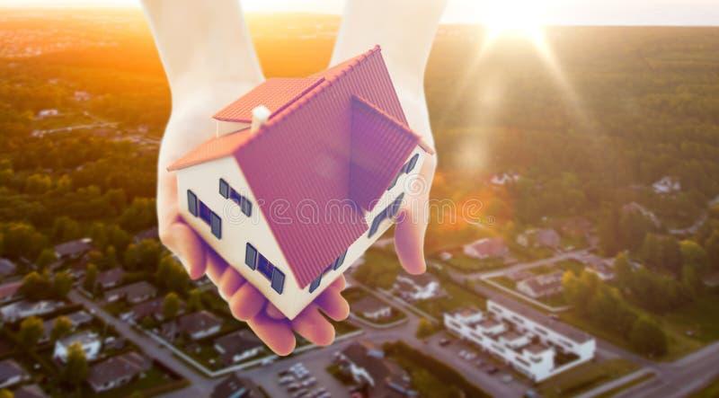 Κλείστε επάνω των χεριών κρατώντας το πρότυπο σπιτιών ή σπιτιών στοκ εικόνες
