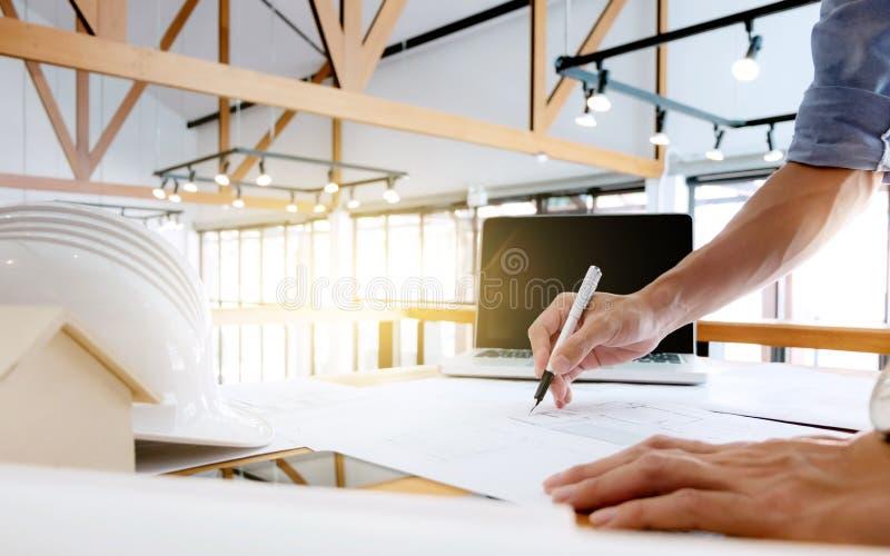 Κλείστε επάνω των χεριών μηχανικών σκιαγραφώντας ένα κατασκευαστικό πρόγραμμα με το lap-top στον εργασιακό χώρο στοκ φωτογραφία