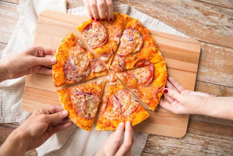 Κλείστε επάνω των χεριών μοιραμένος την πίτσα στον ξύλινο πίνακα στοκ φωτογραφίες