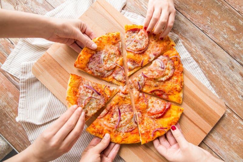 Κλείστε επάνω των χεριών μοιραμένος την πίτσα στον ξύλινο πίνακα στοκ φωτογραφίες με δικαίωμα ελεύθερης χρήσης