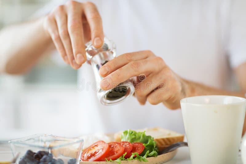 Κλείστε επάνω των χεριών που καρυκεύουν τα τρόφιμα από το μύλο πιπεριών στοκ φωτογραφία με δικαίωμα ελεύθερης χρήσης