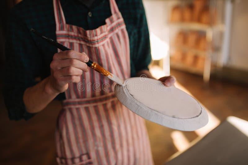 Κλείστε επάνω των χεριών του αγγειοπλάστη κάνοντας τη διακόσμηση στο κεραμικό προϊόν Πιάτο στα χέρια του αρσενικού Νέος καλλιτέχν στοκ εικόνες με δικαίωμα ελεύθερης χρήσης