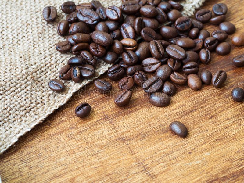 Κλείστε επάνω των ψημένων φασολιών καφέ sackcloth, ξύλινο υπόβαθρο στοκ εικόνες με δικαίωμα ελεύθερης χρήσης