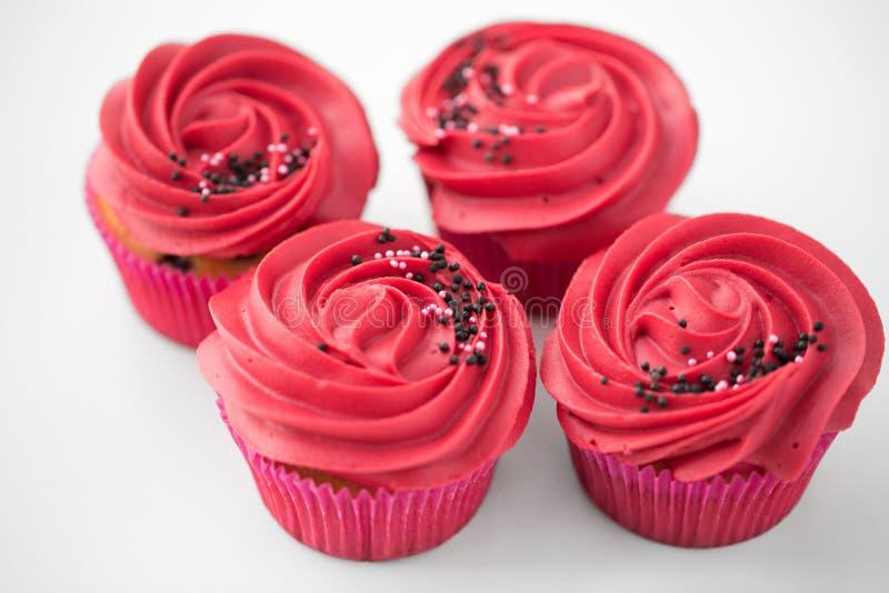 Κλείστε επάνω των cupcakes με το κόκκινο πάγωμα buttercream στοκ εικόνα