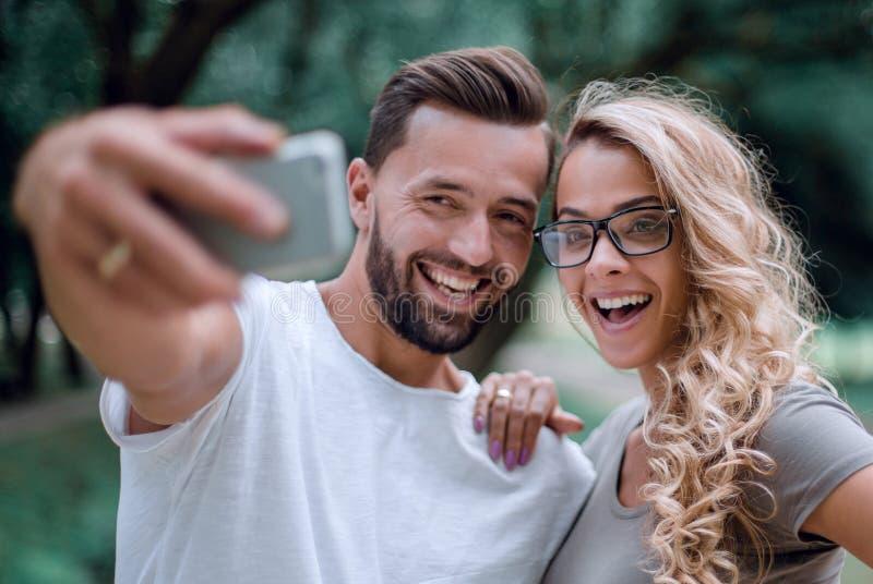κλείστε επάνω χαμογελώντας νέο ζεύγος που παίρνει selfie στο πάρκο πόλεων στοκ φωτογραφίες