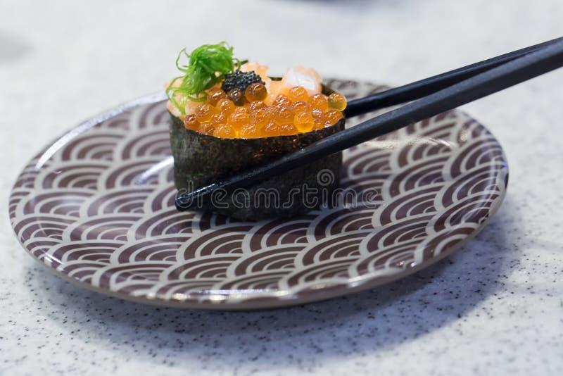 Κλείστε επάνω chopsticks τη λαβή στο φρέσκο σολομό σουσιών Ιαπωνικά τρόφιμα για υγιή στοκ εικόνες