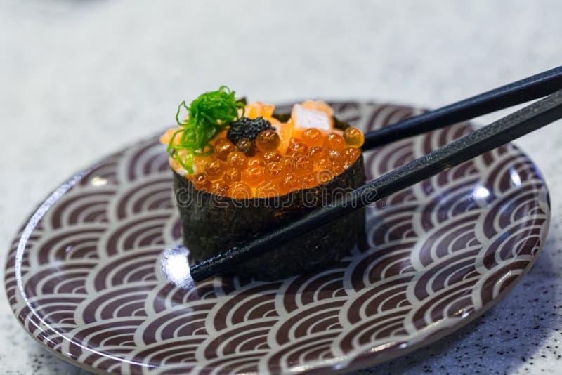 Κλείστε επάνω chopsticks τη λαβή στο φρέσκο σολομό σουσιών Ιαπωνικά τρόφιμα για υγιή στοκ εικόνα με δικαίωμα ελεύθερης χρήσης