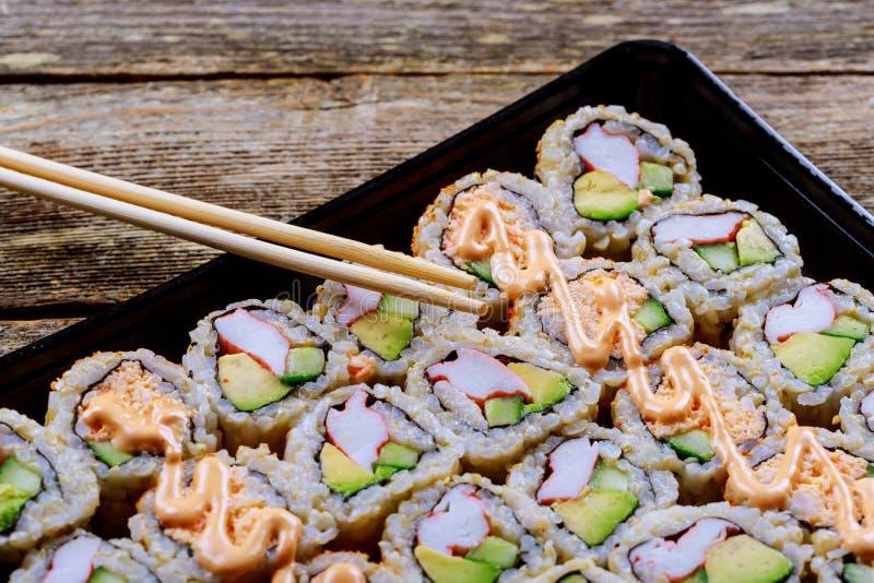 κλείστε επάνω sashimi των σουσιών που τίθενται με chopsticks και τη σόγια - ρόλος σουσιών με το ρόλο σολομών και σουσιών με το κα στοκ φωτογραφίες