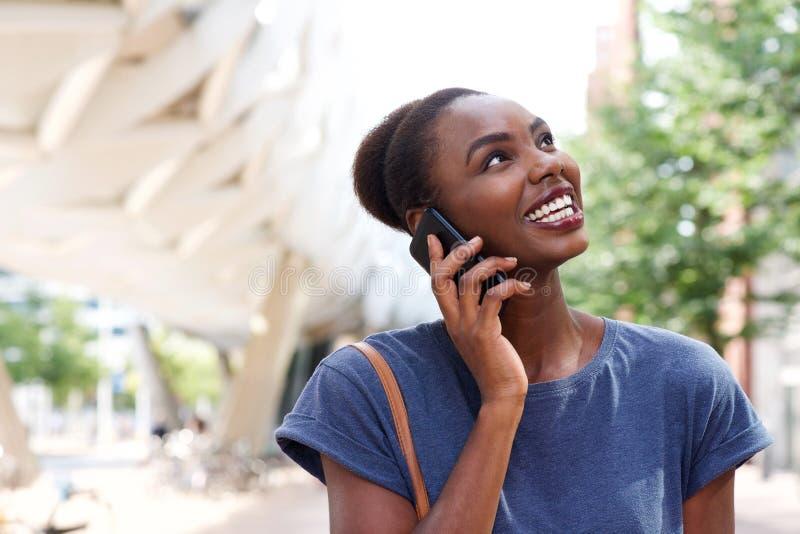 Κλείστε ομιλία γυναικών αφροαμερικάνων επάνω χαμόγελου τη νέα στο κινητό τηλέφωνο στην πόλη στοκ φωτογραφία