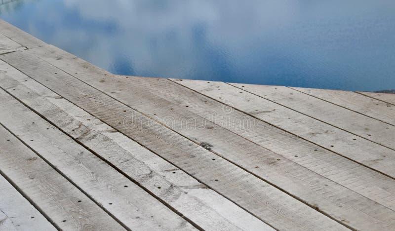 Κλείστε στο ξύλινο πεζούλι στο νερό στοκ φωτογραφία
