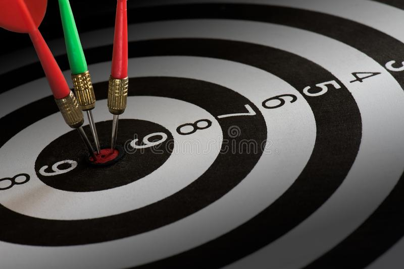Κλείστε τα αυξημένα κόκκινα και πράσινα βέλη βελών στο κέντρο του dartboard, της μεταφοράς στην επιτυχία στόχων και της έννοιας ν στοκ φωτογραφία με δικαίωμα ελεύθερης χρήσης