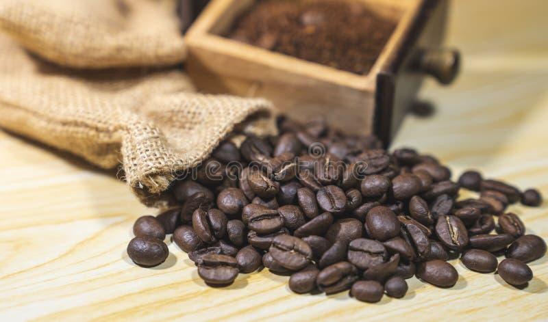 Κλείστε τα επάνω ψημένα φασόλια καφέ στο ξύλινο υπόβαθρο με το β στοκ φωτογραφίες