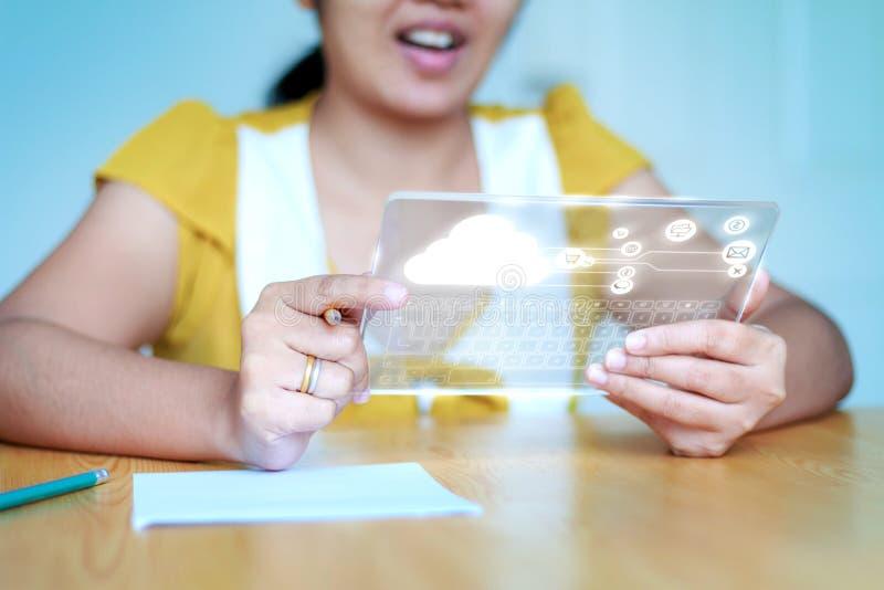 Κλείστε την αυξημένη ασιατική γυναίκα χρησιμοποιώντας τη σαφή ταμπλέτα για το φουτουριστικό cybe στοκ εικόνα