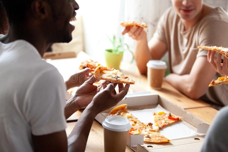 Κλείστε την επάνω καλλιεργημένη εικόνα των διαφορετικών φίλων που τρώνε την πίτσα στοκ φωτογραφίες