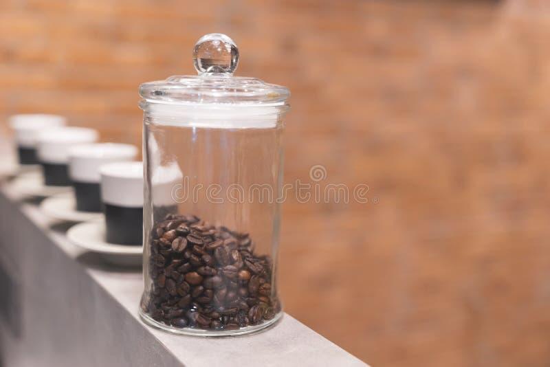 Κλείστε το επάνω ψημένο φασόλι καφέ στο σαφές εμπορευματοκιβώτιο με τα κεραμικά φλυτζάνια στο υπόβαθρο στοκ εικόνες