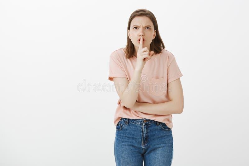 Κλείστε το στόμα σας, κρατήστε σιωπηλός Το πορτρέτο η η γυναίκα στη ρόδινα μπλούζα και τα τζιν, που λέει shh κάνοντας shush στοκ εικόνες με δικαίωμα ελεύθερης χρήσης