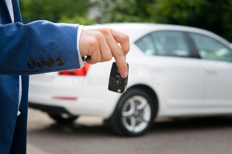 Κλειδί αυτοκινήτων στα χέρια στο άσπρο αυτόματο υπόβαθρο στοκ φωτογραφία με δικαίωμα ελεύθερης χρήσης