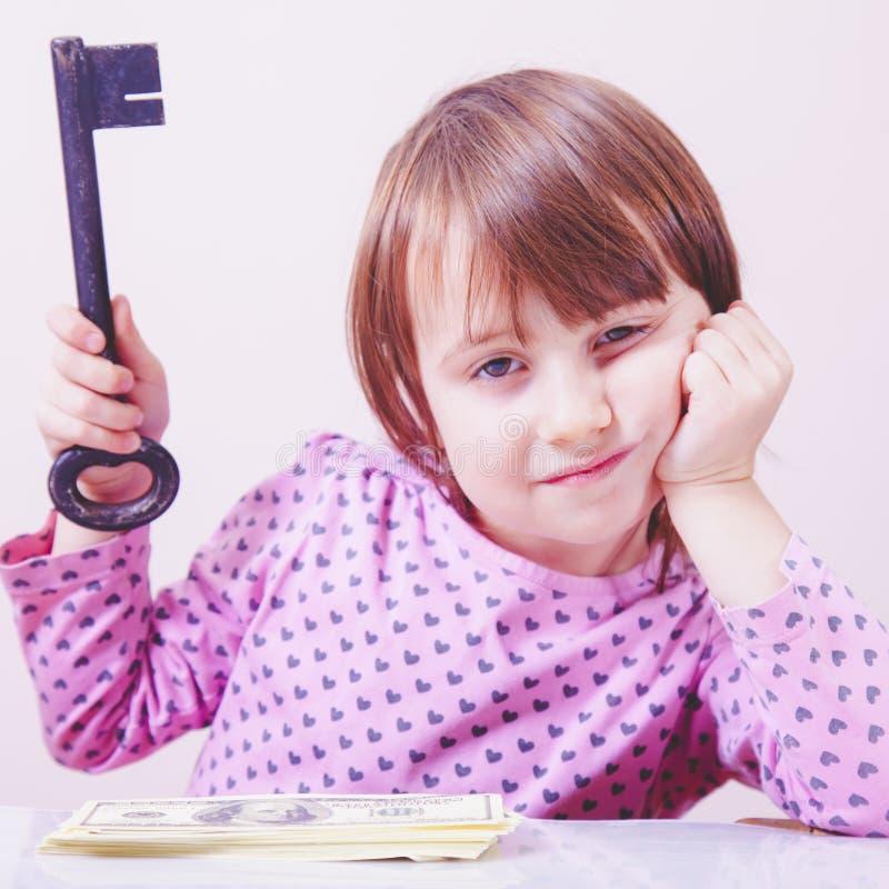 Κλειδί για την επιτυχία Χαριτωμένο μικρό κορίτσι που κρατά βασικό ως σύμβολο του πλούτου και της ασφάλειας στοκ εικόνες