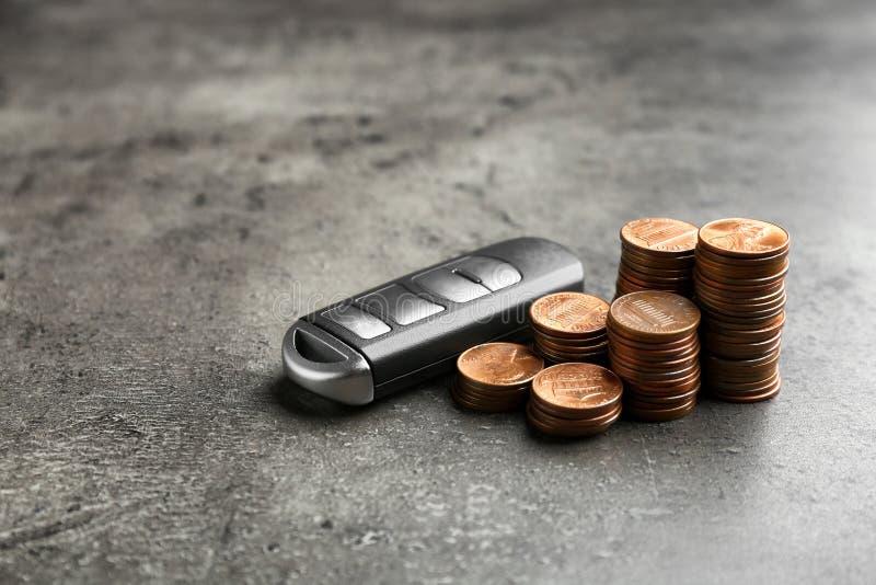 Κλειδί και νομίσματα αυτοκινήτων στο γκρίζο υπόβαθρο στοκ φωτογραφίες
