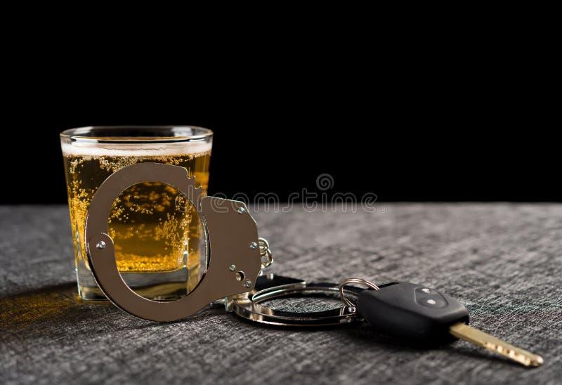 Κλειδί και χειροπέδες αυτοκινήτων μπροστά από το φλυτζάνι της μπύρας στοκ εικόνες