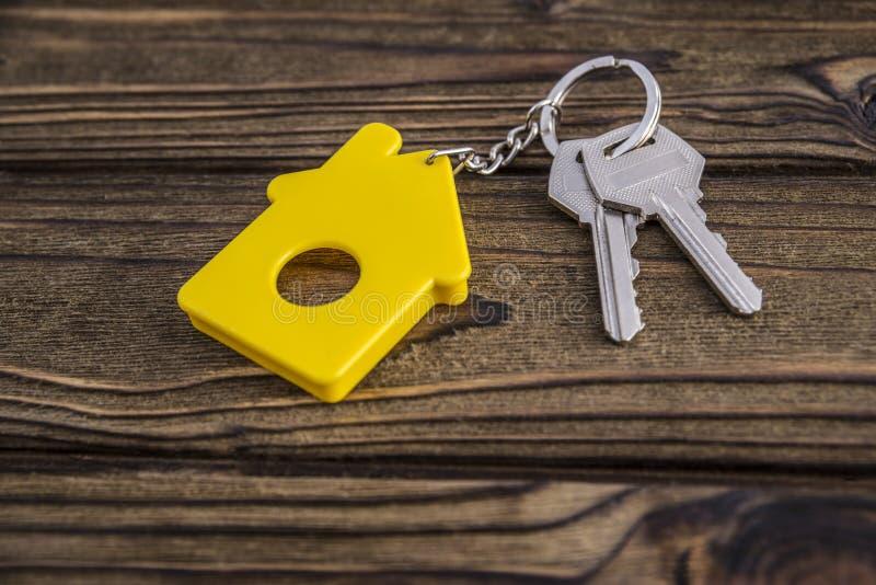 Κλειδί με το κίτρινο διαμορφωμένο σπίτι keychain στην αλυσίδα στο ξύλινο υπόβαθρο σύστασης στοκ εικόνες