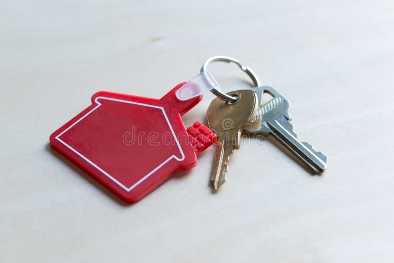 Κλειδί σπιτιών με την κόκκινη μορφή σπιτιών keychain στοκ εικόνες με δικαίωμα ελεύθερης χρήσης