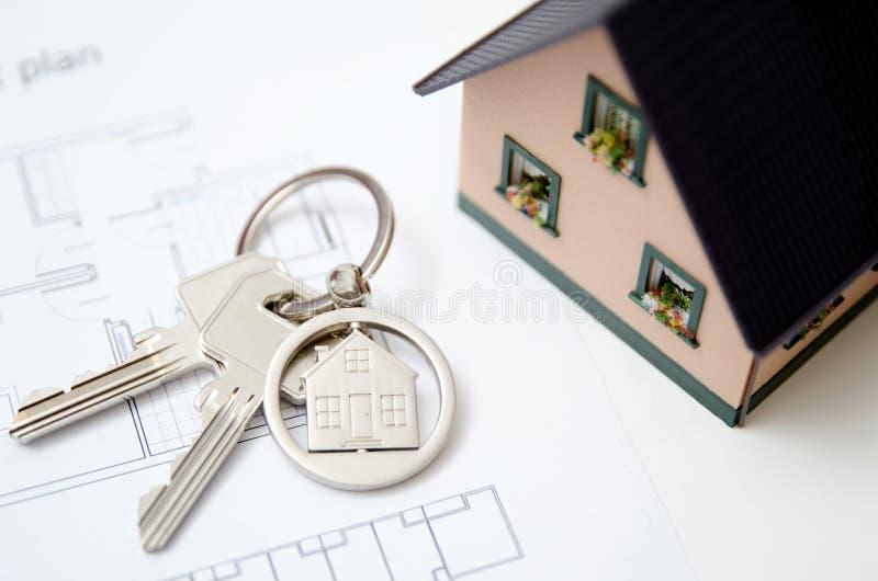 Κλειδί σπιτιών σε ένα διαμορφωμένο σπίτι κρεμαστό κόσμημα στοκ εικόνες