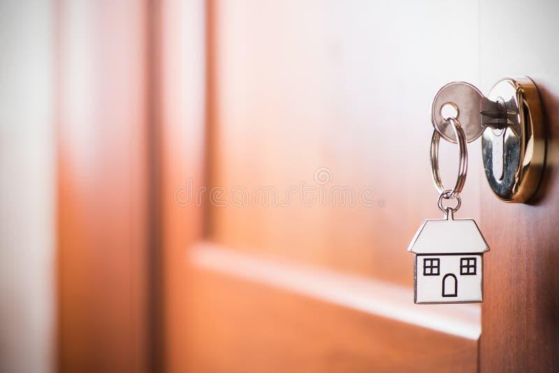 Κλειδί σπιτιών σε μια καφετιά πόρτα σπιτιών στοκ εικόνες με δικαίωμα ελεύθερης χρήσης