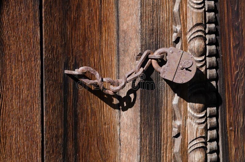 Κλειδαριά σιδήρου σε μια στερεά αλυσίδα που κρεμά σε μια ξύλινη πύλη στοκ φωτογραφίες με δικαίωμα ελεύθερης χρήσης