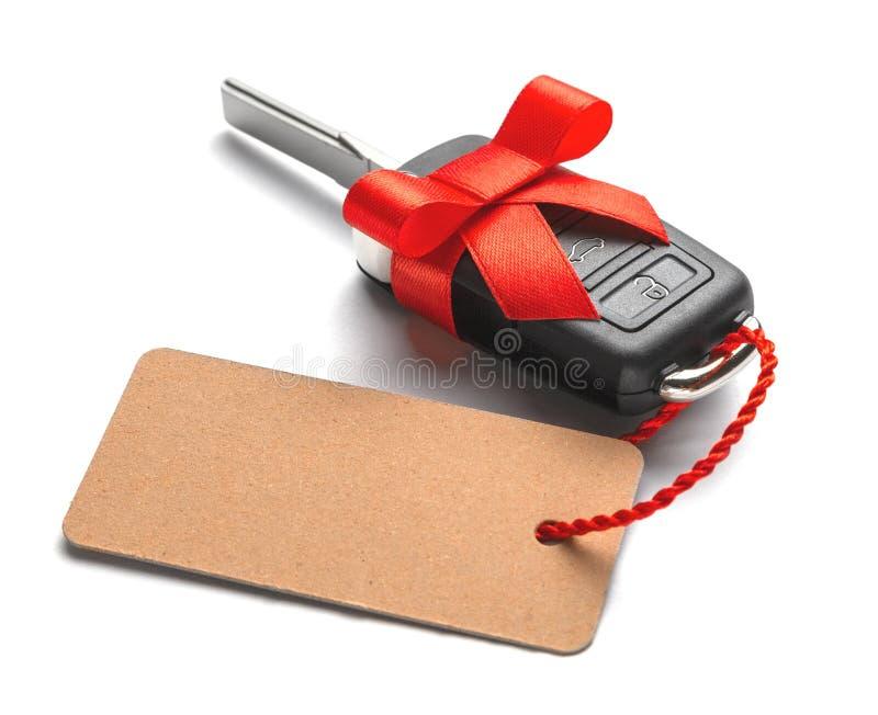 Κλειδιά αυτοκινήτων δώρων με το συναγερμό τηλεχειρισμού με την κόκκινη κορδέλλα με το τόξο και την ετικέτα η ανασκόπηση απομόνωσε στοκ εικόνες