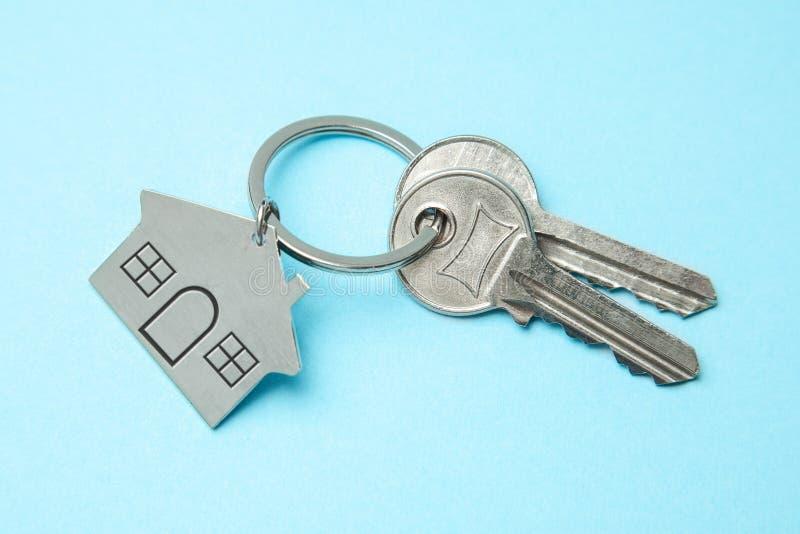 Κλειδιά και ένα σπίτι keychain σε ένα μπλε υπόβαθρο Έννοια της αγοράς ενός σπιτιού, ενοικίαση στοκ φωτογραφία