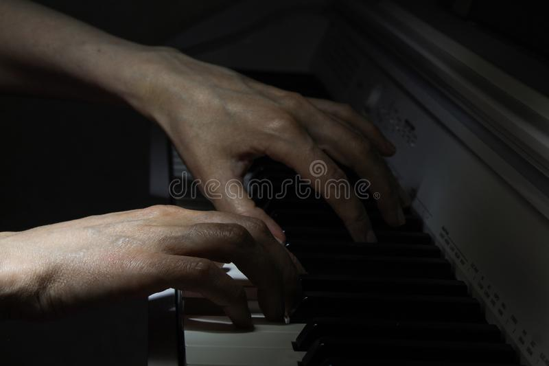 Κλειδιά πιάνων και ανθρώπινη κινηματογράφηση σε πρώτο πλάνο χεριών στοκ φωτογραφίες