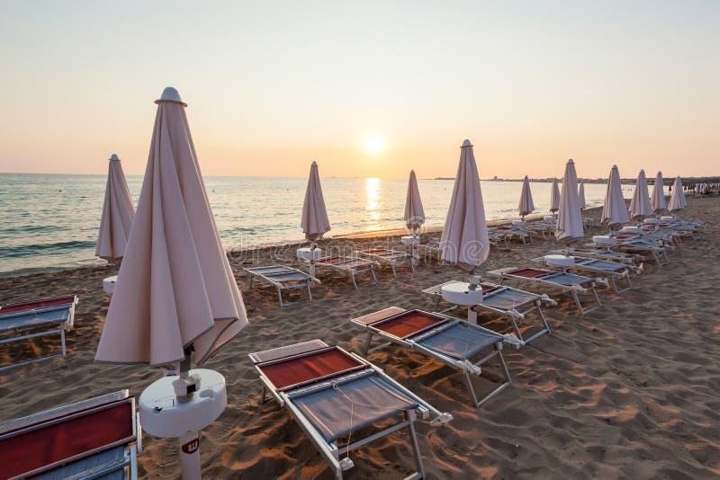 Κλειστές ομπρέλες και καρέκλες στο όμορφο ηλιοβασίλεμα στοκ φωτογραφίες