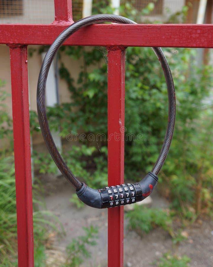 Κλειστή κλειδαριά συνδυασμού σε έναν κόκκινο φράκτη μετάλλων, λουκέτο προστασίας ασφάλειας πυλών στοκ φωτογραφία
