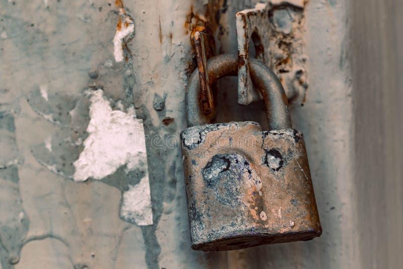 Κλειστή παλαιά σκουριασμένη κλειδαριά Στο υπόβαθρο ενός φράκτη μετάλλων σε μια πόρτα ύφους grunge στοκ εικόνες με δικαίωμα ελεύθερης χρήσης