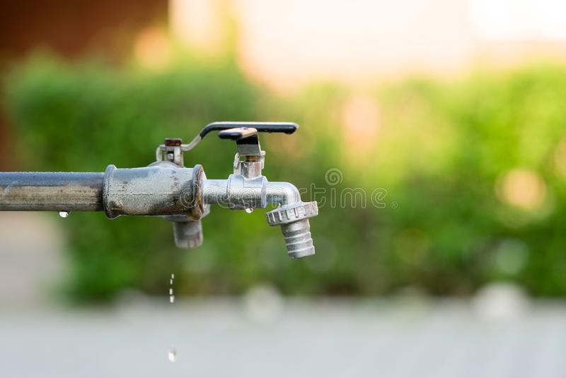 Κλειστή στρόφιγγα ή βρύση νερού στο πράσινο υπόβαθρο κήπων θαμπάδων στοκ εικόνες