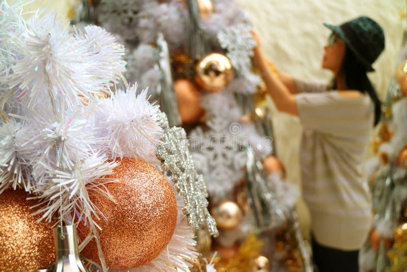 Κλειστός επάνω ακτινοβολήστε χρυσές διακοσμήσεις Χριστουγέννων με το θολωμένο θηλυκό χριστουγεννιάτικο δέντρο διακόσμησης στο υπό στοκ εικόνες