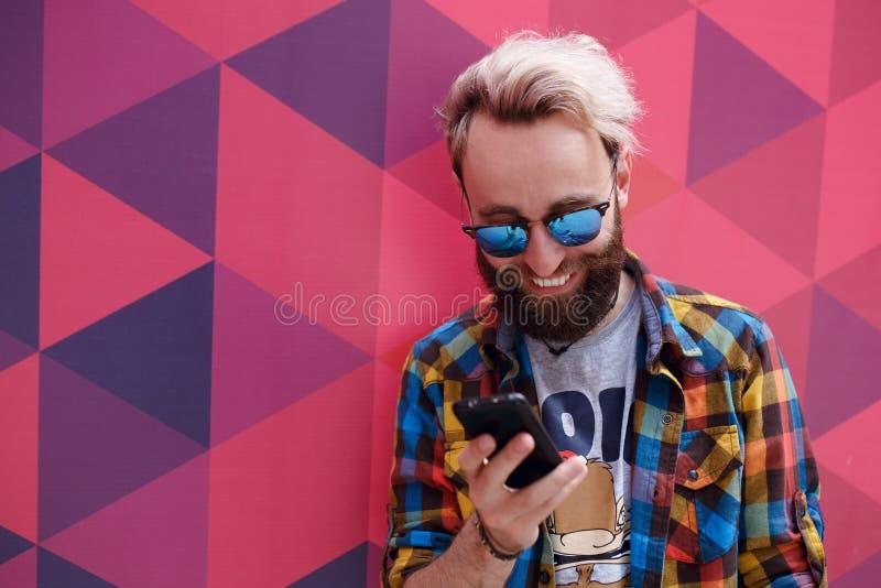 Κλειστός επάνω του ευτυχούς hipster ένας νεαρός άνδρας διάβασε ένα μήνυμα στο τηλέφωνο κυττάρων του, σε ένα ζωηρόχρωμο υπόβαθρο στοκ φωτογραφίες με δικαίωμα ελεύθερης χρήσης